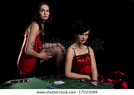 Two woman playing poker at a table with red cabaret dresses on