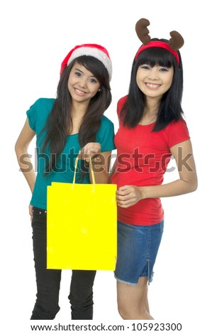 Two woman shopping for christmas sale isolated over white background