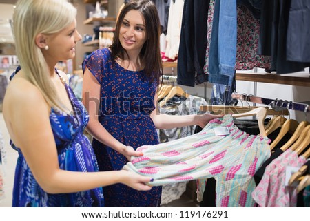 Two woman talking beside clothes rail in shopping mall