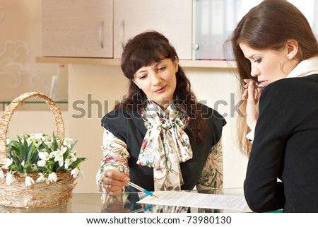 Two woman talking near help desk in reception office