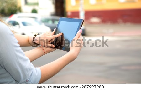 Two woman using touch pad. Close up young female student using touch pad on the city background, freelancer girl working on her digital tablet with big copy space. Two women with touchscreen device.