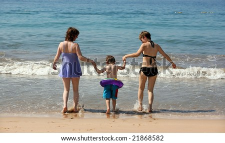 Two women and a baby walking into the ocean