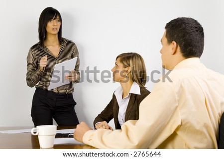 Two women and a man are at the table. One of the women's standing and talking to the rest of people.