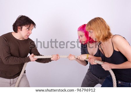 Two women and a man are pulling a rope