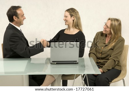 Two women and a man in a meeting at a desk in front of a computer. The man and a woman are shaking hands. Horizontally framed photo.