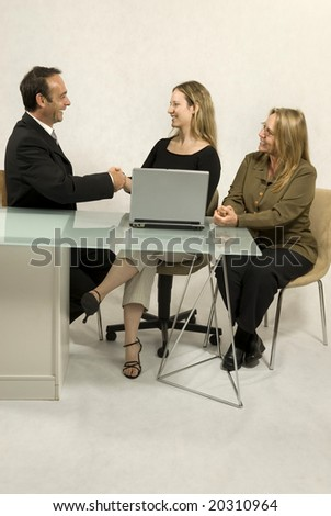 Two women and a man seated at a desk in front of a laptop, they are all smiling and the man and one woman are shaking hands. Vertically framed photo.