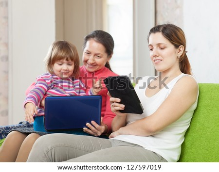 Two women and child  looks electronic devices in home interior - stock photo