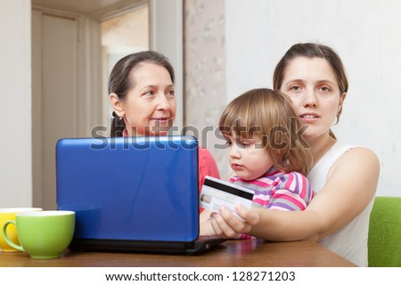 Two women and child shopping online in living room at home