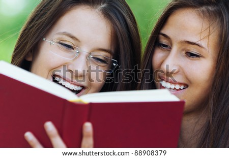 Two women are cheerful beautiful young in the summer the park are holding red book, read
