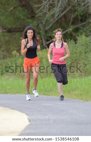 two women are jogging outdoors