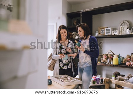 Two women are looking at products in a small shop together.