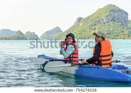 Two women are mother and daughter using a camera take photos on kayak while travel by boat with happy on the sea summer at Ko Wua Ta lap islands in Mu Ko Ang Thong National Park, Surat Thani, Thailand