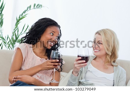 Two women are sitting on a couch and holding wine glasses