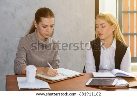 Two women are studying and teaching in the library. - Shutterstock ID 681911182