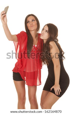 Two women are taking pictures of themselves and making a kissy face.