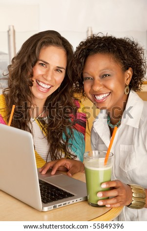 Two women are working on a laptop while enjoying smoothies.  Vertical shot.