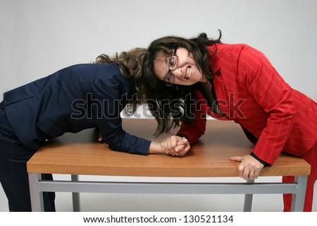 Two women arm wrestling at work on desk