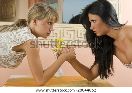 Two women arm wrestling at work on desk on white background