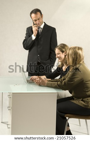Two women at a desk with a computer and a man standing next to them on a cell phone. Vertically framed photo.