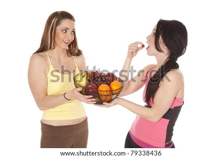 Two women being healthy eating fruit.