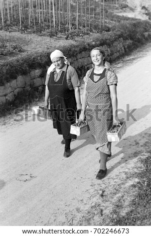 Two women carrying baskets of strawberries