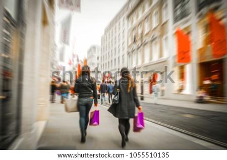 Two women carrying shopping bags past fashion retail shops in London