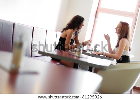 Two women chatting in a restaurant, having fun
