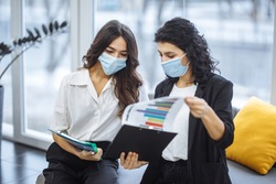 Two women checking charts and discussing business trends in the office. Females colleagues wearing medical masks sit on the couch at a working place. Coronavirus prevention. Colaboration concept