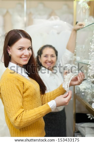 Two women  chooses bridal accessories in wedding boutique