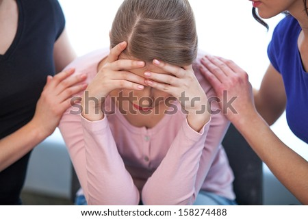 Two women comforting crying girl. Close up of crying girl, who covers her face with both hands