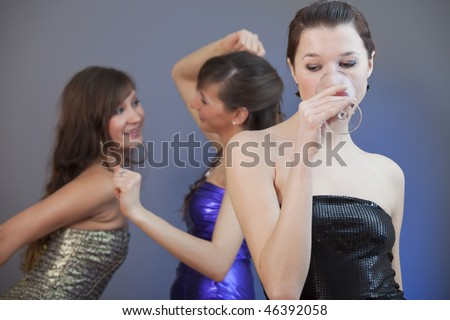 two women dancing - another one drinking wine in bad mood - stock photo