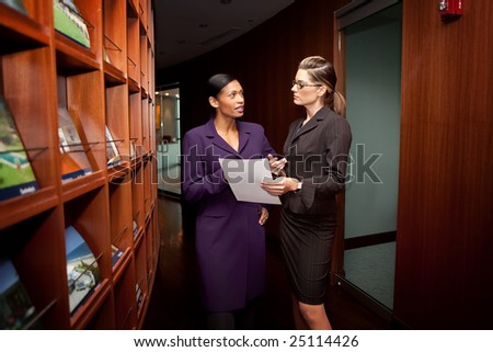 Two women discussing project in corporate building