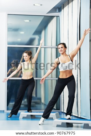 two women doing aerobics with step board in fitness health club