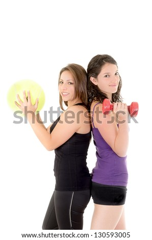 Two women doing exercises with barbell and ball isolated on white background