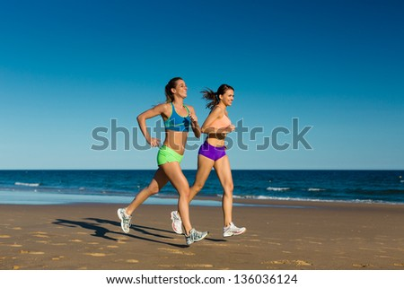 two women doing sport, jogging on the beach in their vacation on the sea