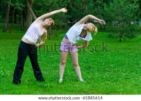 two women doing yoga in park