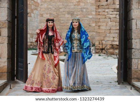 Two women dressed in the traditional Azeri  dress are walking through the narrow street