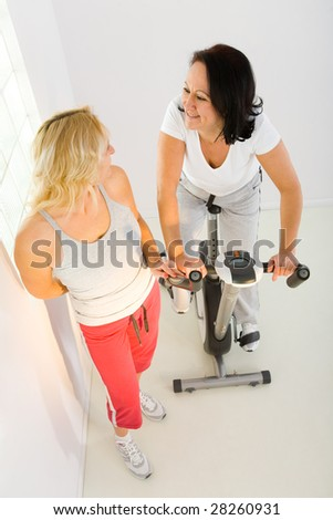 Two women dressed sportswear. One of them exercising on bike. High angle view.