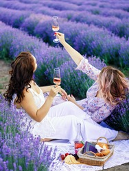 two women drink wine in lavender field, picnic, blurred background