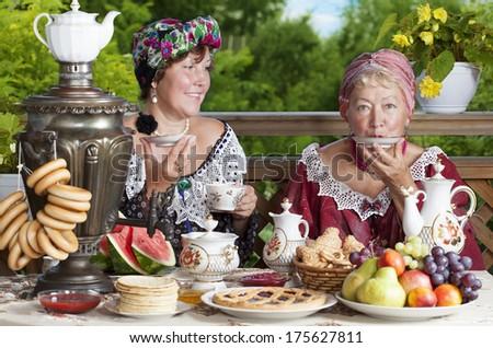 Two women drinking tea outdoors. Kustodiev Russian artist style, beginning of the last century