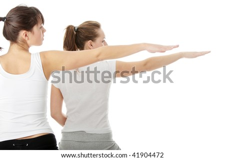 Two women exercising, isolated on white background