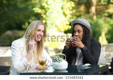 Two women friends drinking tea at an outdoors cafe