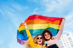 Two women friends hanging out in the city waving LGBT with pride flag