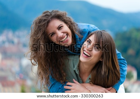 Two women friends laughing and hugging outdoors.