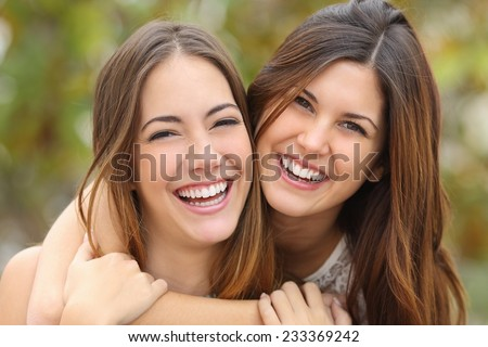Two women friends laughing with a perfect white teeth with a green background Foto stock ©