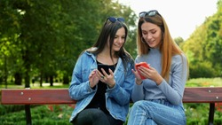 Two women friends sitting on a bench in park and using mobile phone, choosing pictures for social media app