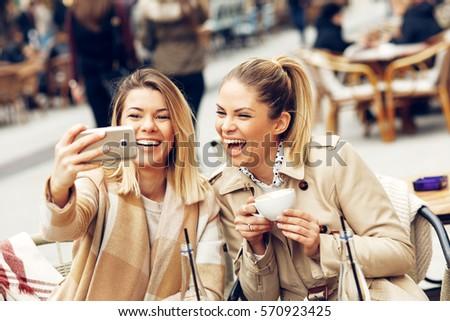 Two women friends taking a selfie in cafe #570923425