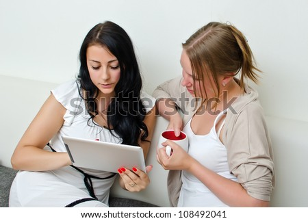 Two women friends using a tablet PC computer