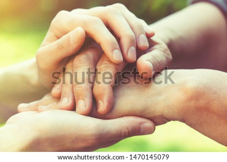 two women generations, family relationship, senior people care, close up young female hands holding wrinkled hand of senior woman, blurred green nature background