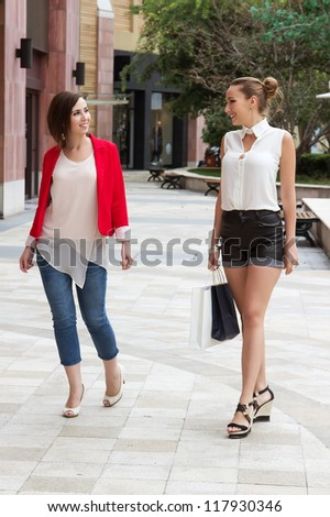 Two women go shopping together. Group of young girls walking on the street and talk